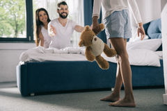 Girl in pajamas holding teddy bear and walking to parents sitting on bed Royalty Free Stock Photo