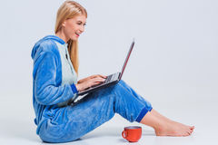 Girl in pajamas with a laptop. Lying on the floor. studying or doing online shopping. work from home. Satisfied and smiling stock photography