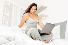 Girl in pajamas with laptop Royalty Free Stock Photo