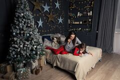 A girl in pajamas lies on the bed and writes a letter to Santa Claus or grandfather frost on the background of a Christmas tree