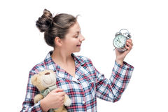 Girl in pajamas looks at alarm clock and holds in hand a teddy Royalty Free Stock Image