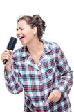 A girl in pajamas loves a song to sing. Instead of a microphone a hairbrush on a white background Royalty Free Stock Photo