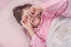 The girl in a pajamas lying in a bed rubs eyes Stock Photo