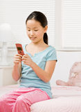 Girl in pajamas text messaging with cell phone Stock Images