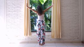 Girl in pajamas unveil the curtains in the morning in tropical island. Girl in pajamas unveil the curtains in the morning in garden stock photography