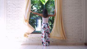 Girl in pajamas unveil the curtains in the morning in tropical island. Girl unveil the curtains in the morning stock photography