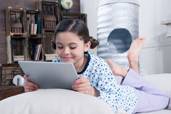 Girl in pajamas using digital tablet on bed Royalty Free Stock Photo