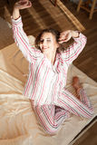Girl in pajamas woke up in the morning is sitting on a bed Royalty Free Stock Photography