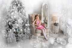 Girl in a pale pink dress sitting in a chair at the Christmas tree Stock Image
