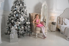 Girl in a pale pink dress sitting in a chair at the Christmas tree Royalty Free Stock Image