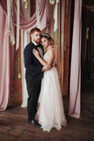 Girl in the pale pink wedding dress and bearded red man standing near the ceremonial arches with fabrics, fresh flowers. Girl in the pale pink wedding dress and Stock Photos