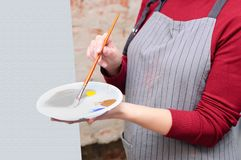 Girl with a palette of colors in her hands. In Art workshop royalty free stock photo