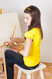 Girl with a palette of paints Stock Photography