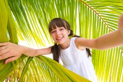 Girl and palm leaves. Happy young girl looking through green palm leaves on tropical beach Royalty Free Stock Photos