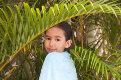 Girl in palm-tree. Little girl wrapped in towel with palmtree leaf Stock Photos