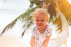 Girl on palm tree. Little girl sitting on a palm tree stock image