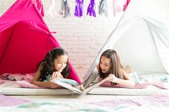 Girl Pals Looking At Picture Book While Lying In Tents. During sleepover at home royalty free stock image