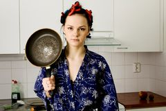 Girl With Pan. Young woman staying in the kitchen with pan royalty free stock photos