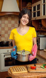 Girl with pan cooking dinner in the kitchen. Facial expression Royalty Free Stock Photography