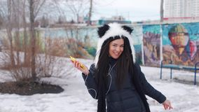 A girl in a panda hat listens to music in the city stock video footage