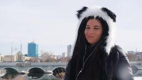 A girl in a panda hat listens to music in the city. Happy young casual woman listening music in park in sunset, trendy urban fashion stock video footage