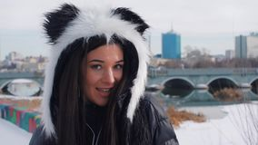 A girl in a panda hat listens to music in the city stock footage