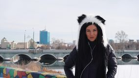 A girl in a panda hat listens to music in the city stock video