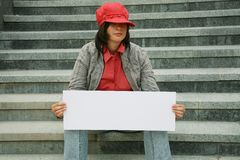 Girl with a paper for the announcement in hand. The girl with a paper for the announcement in hands sitting at steps Stock Photos