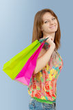 A girl with paper bags looking at camera and smiling Royalty Free Stock Photos