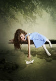 Girl and paper boat. Girl with long hair lying on the tree and playing with paper boats Stock Photos