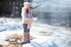 Girl with paper boat. Near winter river Stock Images