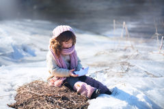Girl with paper boat. Near winter river Royalty Free Stock Photo