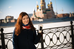 Girl with a paper cup of coffee. Photo girl with a paper cup of coffee on the background of the city Stock Photography