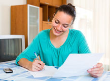 Girl with papers at the table at home Stock Images