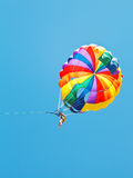 Girl parakiting on parachute in blue sky Royalty Free Stock Image