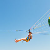 Girl parasailing on parachute in blue sky Royalty Free Stock Photography