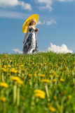 Girl with parasol looking into. Young girl with yellow parasol looking into camera on a meadow in spring royalty free stock image