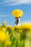 Girl with parasol looking away,. Girl with yellow parasol on meadow in spring, blurred dandelions in foreground royalty free stock photography