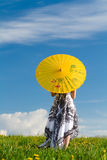 Girl with parasol looking away. Girl with yellow parasol looking away on meadow in spring stock images