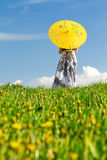 Girl with parasol looking away,. Girl with yellow parasol looking away from camera, lower half of the photo contains blurred meadow stock images