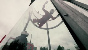 Girl paratrooper performing a parachute jumping in a wind tunnel stock video footage