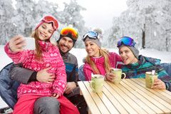 Girl with parents and brother making selfie at winter holiday. In cafe Royalty Free Stock Photo