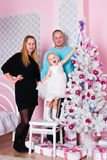 The little girl with parents a white Christmas fir-tree Stock Photo