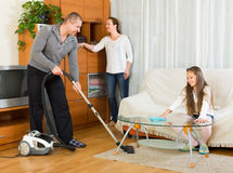 Girl with parents cleaning at home Stock Photo