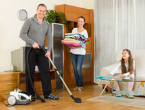 Girl with parents cleaning at home Stock Images