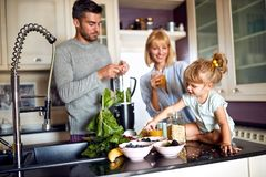 Girl with parents having breakfast royalty free stock photography