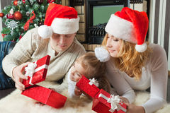 Girl with parents looking gifts nearthe christmas tree Stock Image