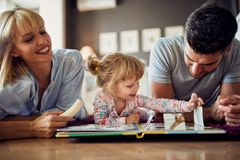 Girl with parents playing and eating banana royalty free stock photography