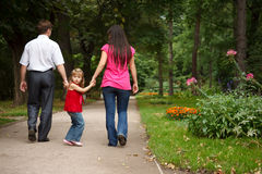 Girl with parents walks in summer garden Royalty Free Stock Photo