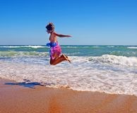 Girl in pareo jumping on the coastline Stock Photos